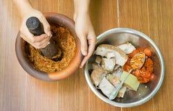 与Crushing Ingredient夫人的在岩石罐的传统泰国食物 库存照片