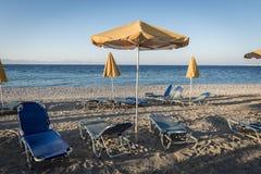 与deckchairs和一把黄色遮阳伞的空的海滩 库存照片