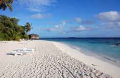 与deckchairs的白色沙子海滩 图库摄影