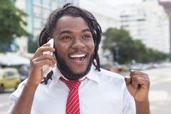 与dreadlocks的愉快的非裔美国人的商人在电话 免版税库存照片