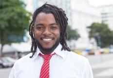 与dreadlocks的笑的非裔美国人的商人在城市 免版税图库摄影