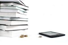 与EBook的看书 便宜的教育的概念 堆书和硬币在白色背景 免版税库存照片