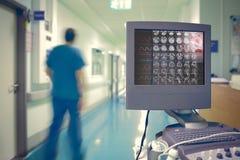 与ECG的医疗显示器和在背景的脑部扫描蓝色 免版税库存图片