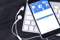 与Facebook主页的苹果计算机iPhone 7在显示器屏幕上 最大的社会网络网站的Facebook一 facebook.com主页 库存图片