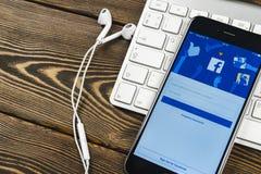 与Facebook主页的苹果计算机iPhone 7在显示器屏幕上 最大的社会网络网站的Facebook一 facebook.com主页 库存照片
