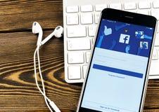 与Facebook主页的苹果计算机iPhone 7在显示器屏幕上 最大的社会网络网站的Facebook一 facebook.com主页 免版税库存图片