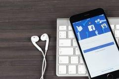 与Facebook主页的苹果计算机iPhone 7在显示器屏幕上 最大的社会网络网站的Facebook一 facebook.com主页 免版税库存照片