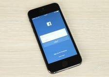 与Facebook注册页的IPhone在它的在木背景的屏幕上 免版税库存图片