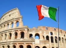 与Flavian圆形露天剧场的意大利旗子或罗马斗兽场在背景中 库存照片