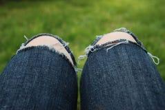 与fuzzi牛仔裤的膝盖在绿草后院 放松Holliday概念 新的成人 免版税库存图片