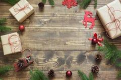 与giftbox、鹿、红色球、锥体和装饰的圣诞节构成在有拷贝空间的木板 免版税库存照片