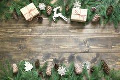 与giftbox、鹿、自然装饰和锥体的圣诞节构成在有拷贝空间的木板 平的位置 免版税库存照片