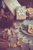 与giftbox,碗用核桃,杏仁,桂香,在木桌上的雪花的圣诞节静物画 顶视图 免版税库存照片