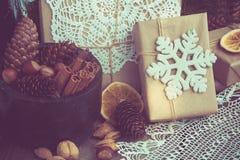 与giftbox,碗用核桃,杏仁,桂香,在木桌上的雪花的圣诞节静物画 顶视图 库存照片