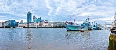 与HMS贝尔法斯特和英国国旗的现代伦敦都市风景 库存图片