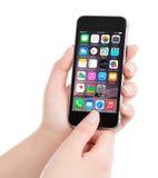 与iOS 8的苹果计算机空间灰色iPhone 5S在显示homescreen 免版税库存图片