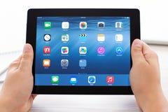 与IOS 8的IPad在屏幕上在男性手上 库存图片