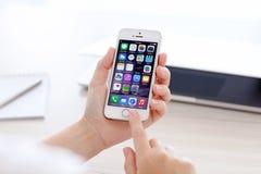 与IOS 8的IPhone 5S在MacBook背景的一只手上  免版税库存照片