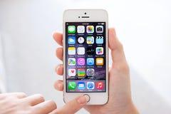 与IOS 8的IPhone 5S金子在女性手上 库存图片