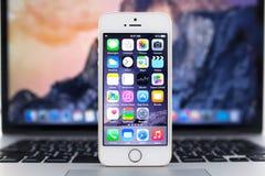 与IOS 8立场的IPhone 5S在赞成MacBook 库存图片