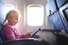与ipad的Gilrl在飞机 免版税库存照片