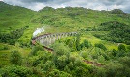 与Jacobite蒸汽的Glenfinnan铁路高架桥,在苏格兰的高地的Lochaber地区 免版税库存照片