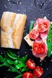 与jamon,芝麻菜,蕃茄,在石板岩黑色背景的乳酪的单片三明治 顶视图 免版税库存照片