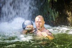 与Kettlebell的Kettlebell教练员在水中 免版税库存图片