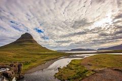 与Kirkjufell火山的夏天多云天在Snaefellsnes半岛海岸  Kirkjufellsfoss瀑布田园诗场面  库存图片
