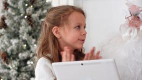 与listenting对一个小女孩的片剂的圣诞老人描述她为圣诞节要的礼物 免版税库存图片