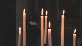 与madonna的雕象的被点燃的蜡烛在背景中 库存照片