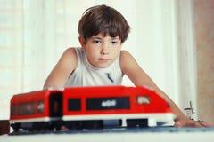 与meccano玩具火车的青春期前的英俊的男孩戏剧 库存照片