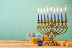 与menorah的光明节庆祝在bokeh背景的木桌上 免版税图库摄影
