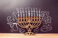 与menorah的创造性的犹太假日光明节背景在有手图画的黑板 图库摄影