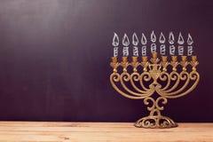 与menorah的犹太假日光明节背景在有手图画的黑板 免版税库存照片