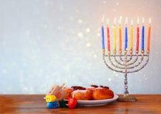 与menorah,在木桌的多福饼的犹太假日光明节 减速火箭的被过滤的图象 免版税库存图片