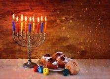 与menorah,在木桌的多福饼的犹太假日光明节 减速火箭的被过滤的图象 免版税库存照片