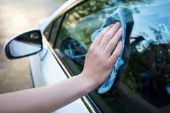 与microfiber布料的男性手清洁车窗 免版税库存图片
