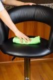 与microfiber旧布的清洁皮革厨房椅子 免版税库存照片