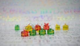 与miniture玻璃红色绿色黄色圣诞节礼物树装饰的发光的圣诞节摄影图片在包装纸 免版税库存图片
