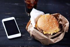 与moblie电话的乳酪汉堡 库存照片