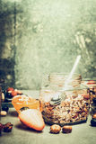 与muesli瓶子的早餐场面在与坚果和莓果的厨房用桌上在土气背景 免版税库存图片