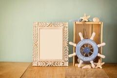 与naurical轮子的老葡萄酒框架在木桌上 葡萄酒被过滤的图象 免版税图库摄影