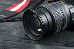 与Nikkor 24-120mm透镜的尼康D800数字式DSLR照相机在黑木背景 免版税库存照片