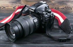 与Nikkor 24-120mm透镜的尼康D800数字式DSLR照相机在黑木背景 免版税图库摄影