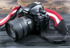 与Nikkor 24-120mm透镜的尼康D800数字式DSLR照相机在黑木背景 免版税库存图片
