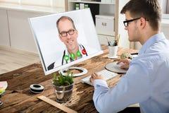 与On Computer医生的商人视讯会议 库存图片