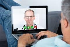 与On Laptop医生的人电视电话会议 免版税图库摄影