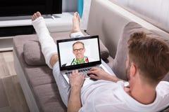 与On Laptop医生的人视讯会议 库存照片
