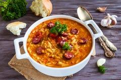 与orzo的蕃茄汤和在白色砂锅的熏制的香肠在木土气桌上 新鲜面包和荷兰芹,葡萄酒匙子 免版税库存照片